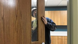 Marcus Schoof with Larson-Danielson wiping down window at Porter County Animal Shelter